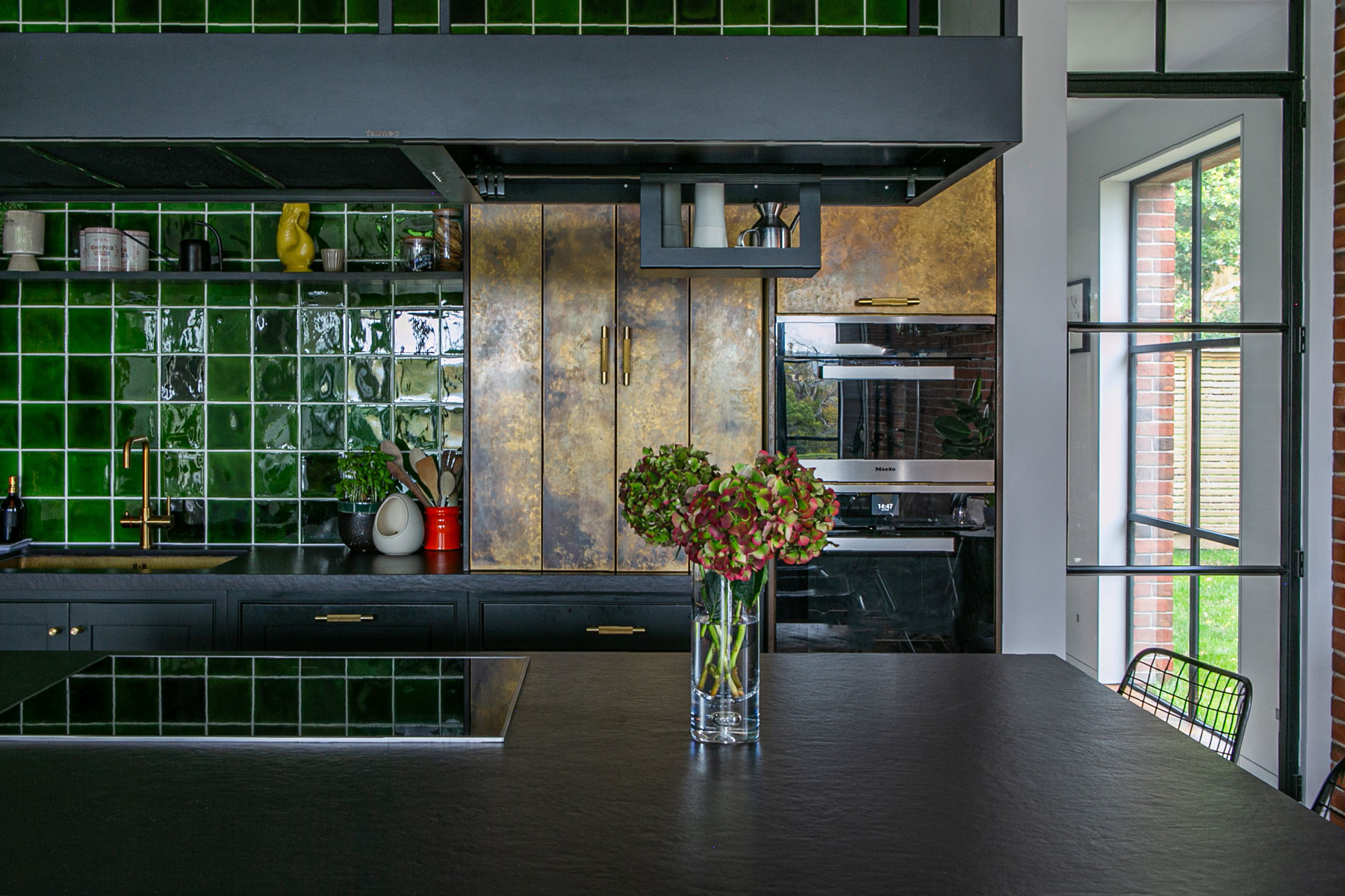 Aged brass and green tiles in bespoke kitchen