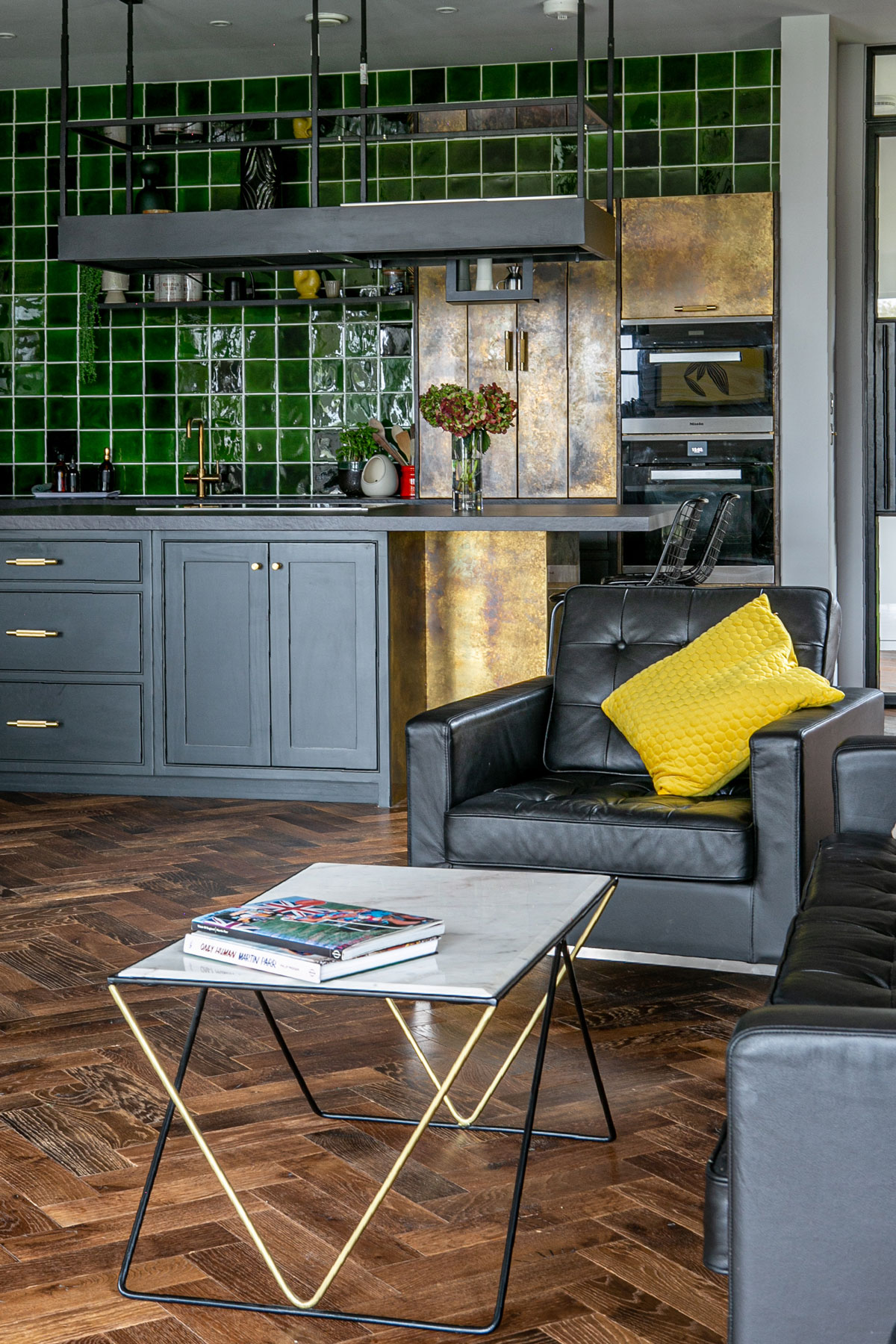 Black armchair and coffee table in open plan kitchen with parquet flooring