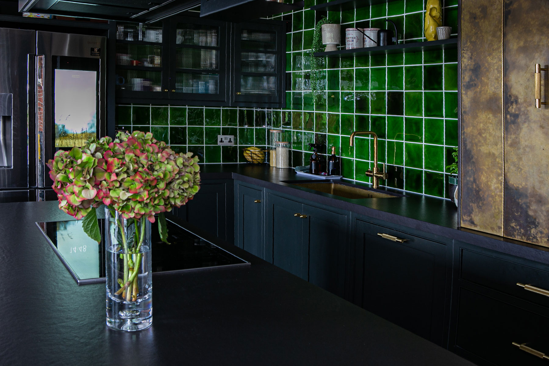 Square green kitchen tiles make large backsplash