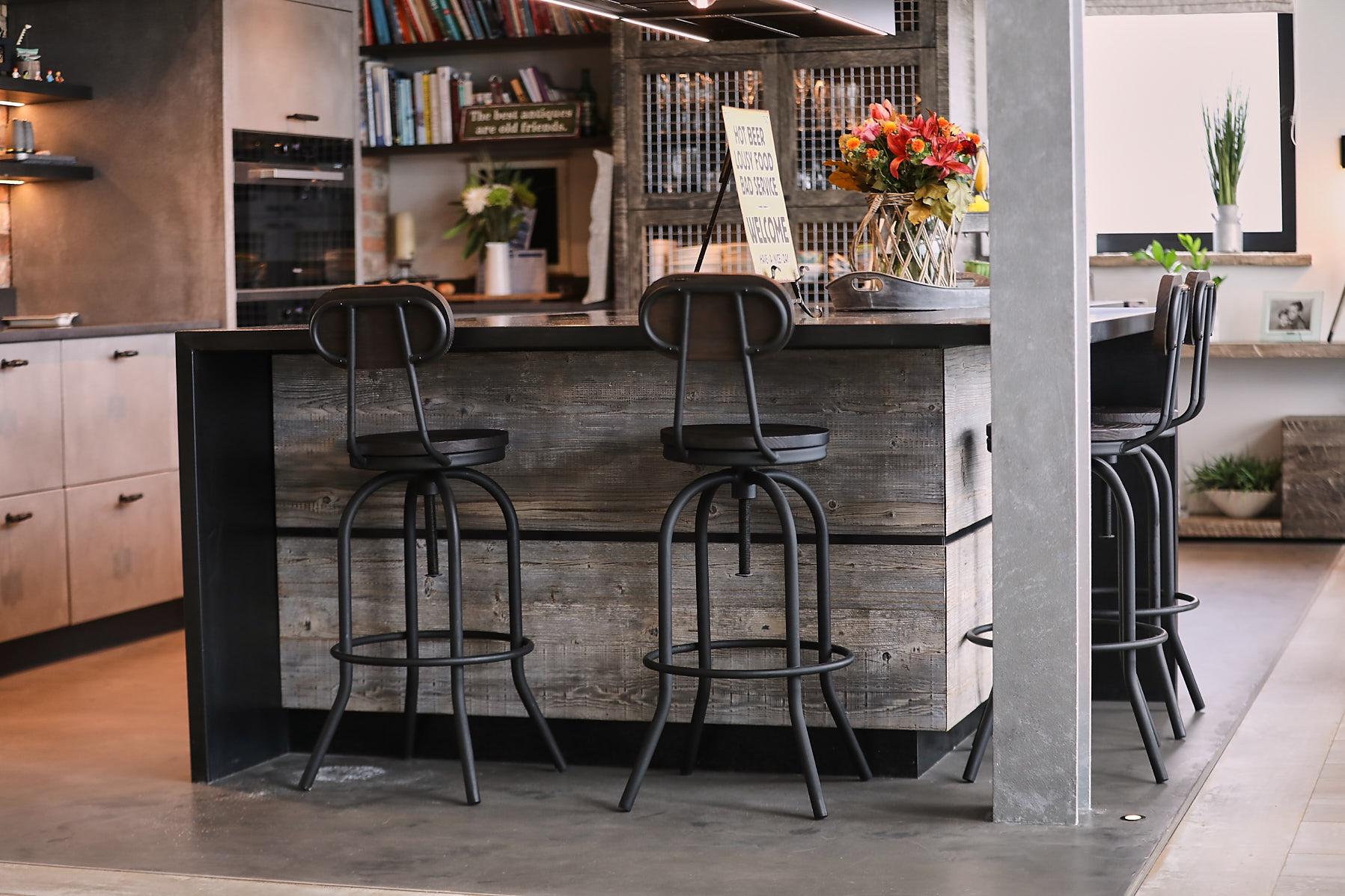 Metal bar stools sit under zinc worktop on kitchen island
