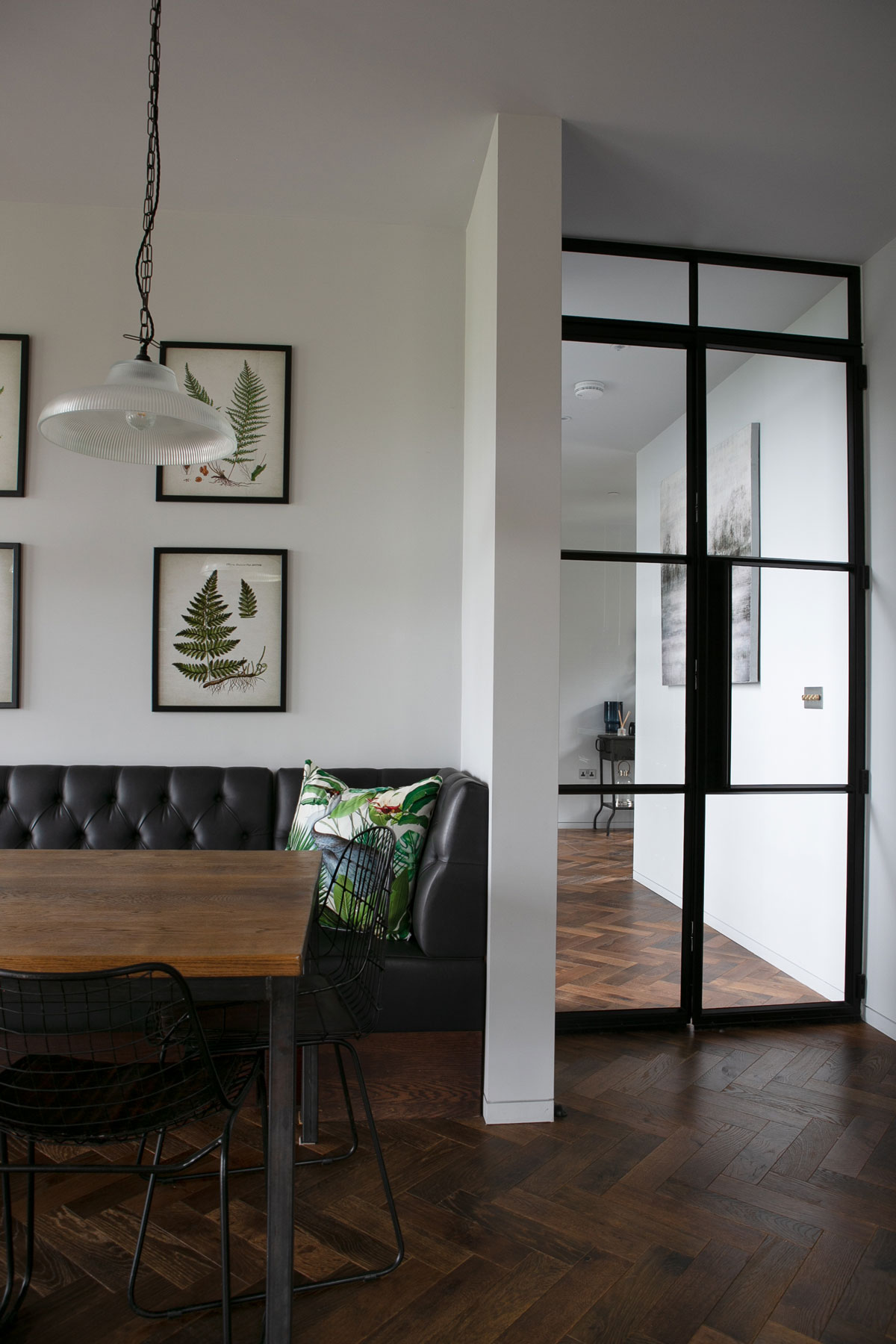 Crittall door in open plan kitchen with parquet flooring