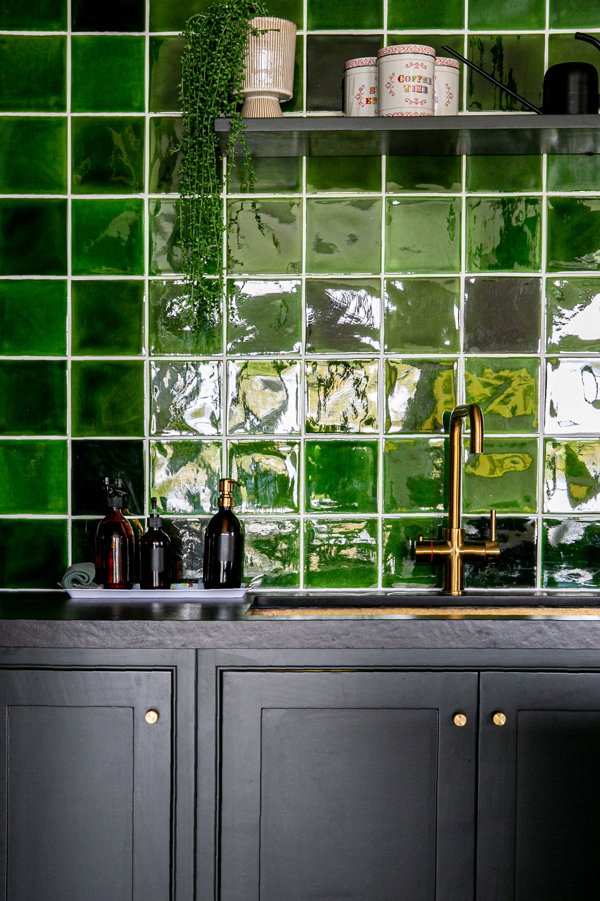 Kitchen cabinets painted in little greene lamp black with green tile back splash