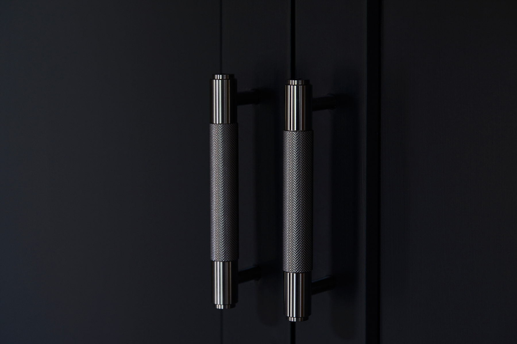 Knurled Buster + Punch brass kitchen handles on painted dark black cabinets