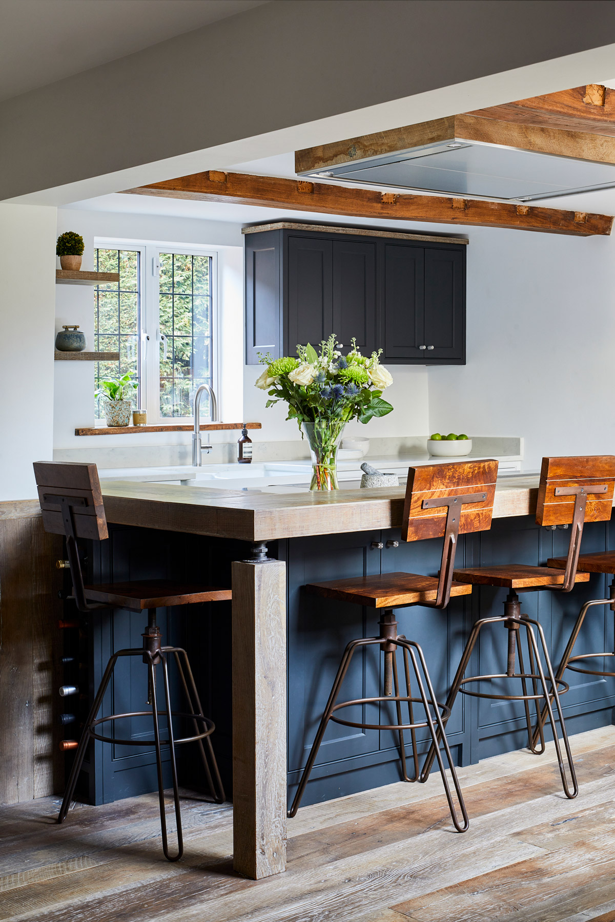 Industrial bar stools under dark kitchen island with reclaimed oak worktop