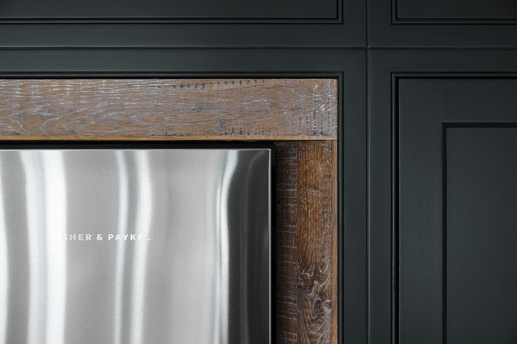 Fisher + Paykel stainless steel fridge freezer against reclaimed oak surround