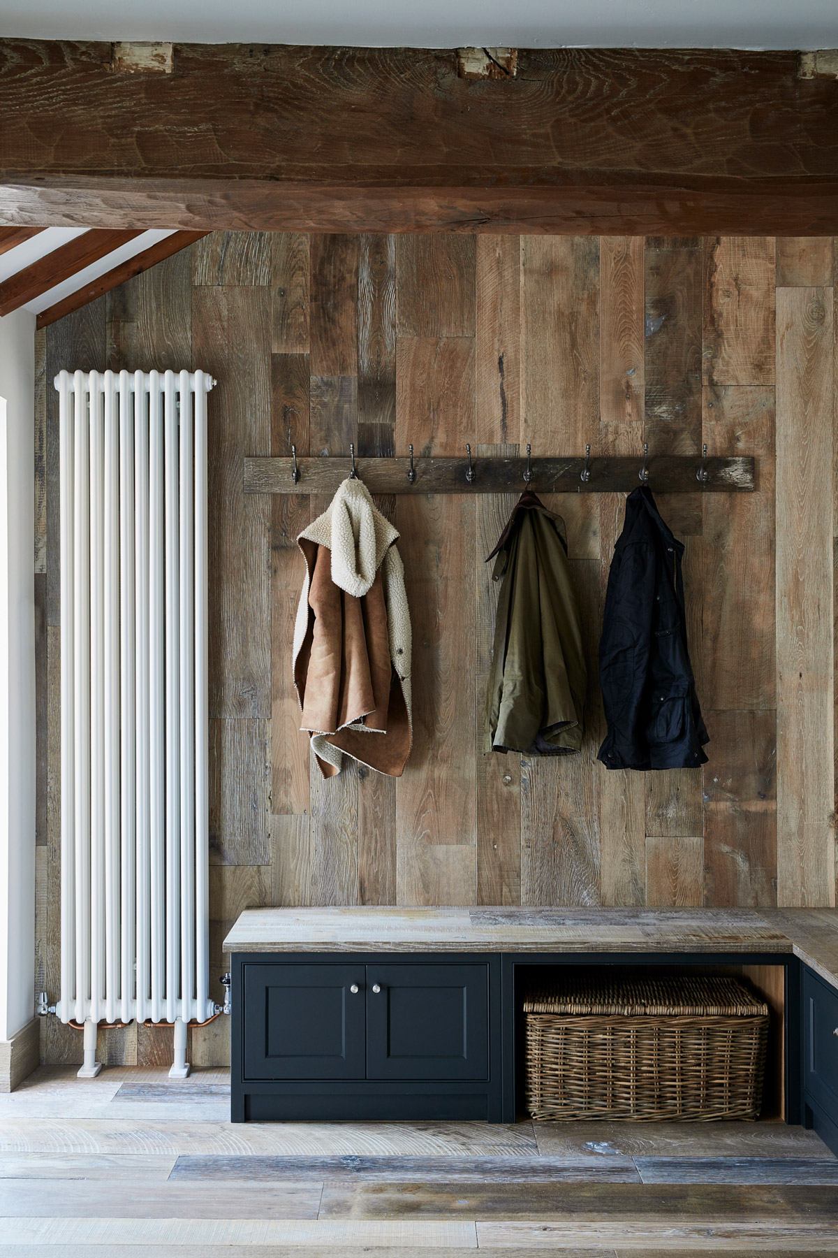 Coat hook on reclaimed oak cladded wall and painted bespoke boot cupboards