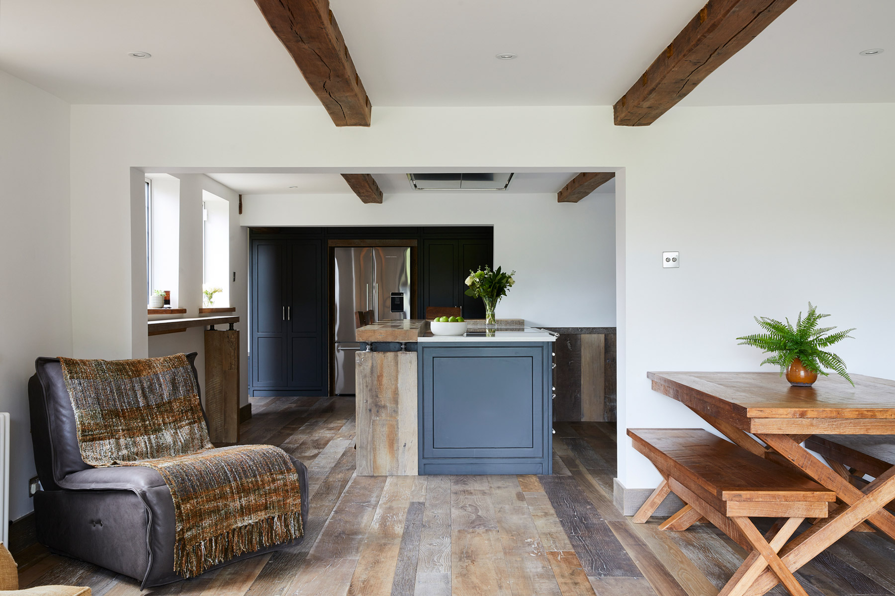Open plan kitchen with reclaimed flooring and bespoke painted kitchen
