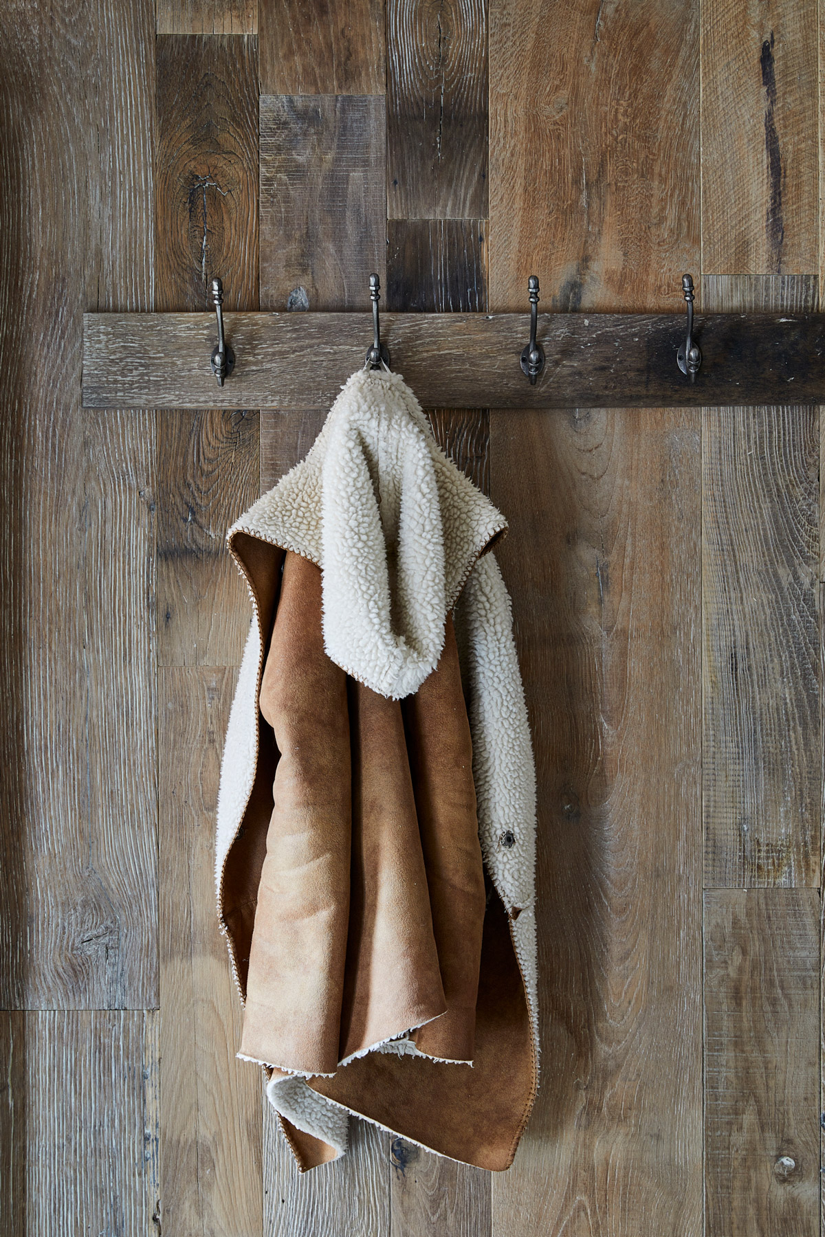 Coat hung on wall covered in reclaimed oak cladding