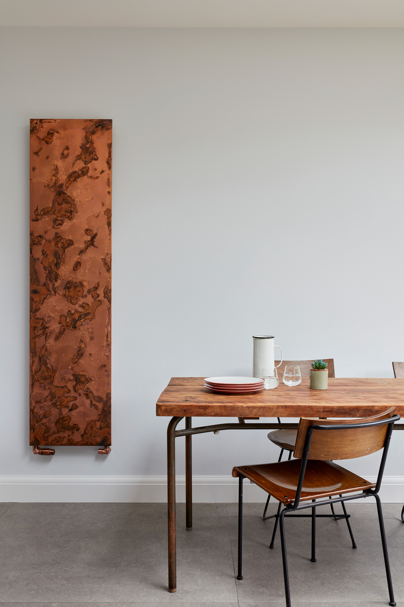 Exposed copper radiator with reclaimed oak table