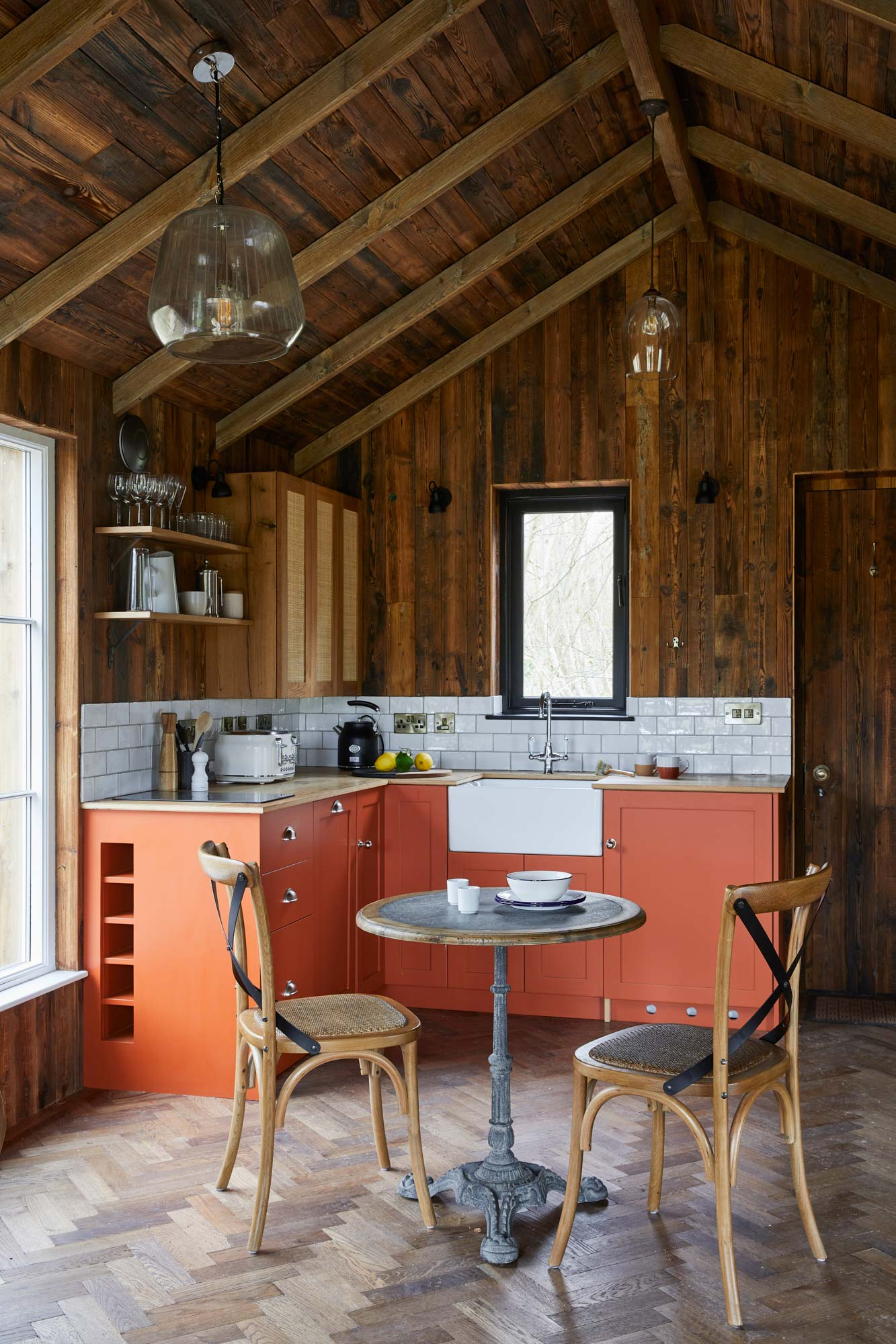 Orange kitchen in treehouse with reclaimed wall clad