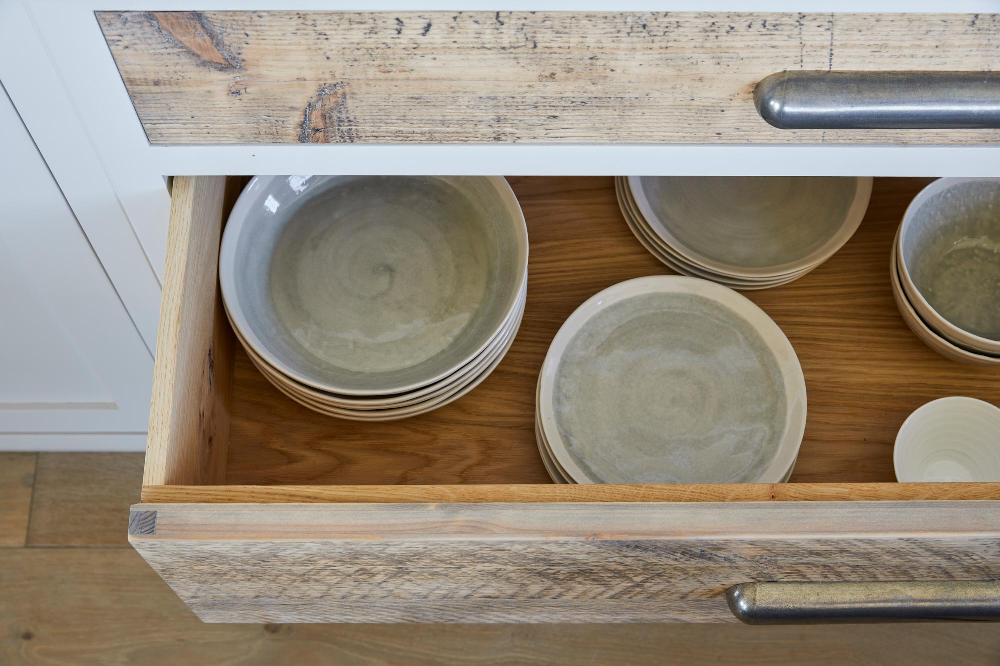 Ceramic bowls and plates in deep kitchen pan drawers