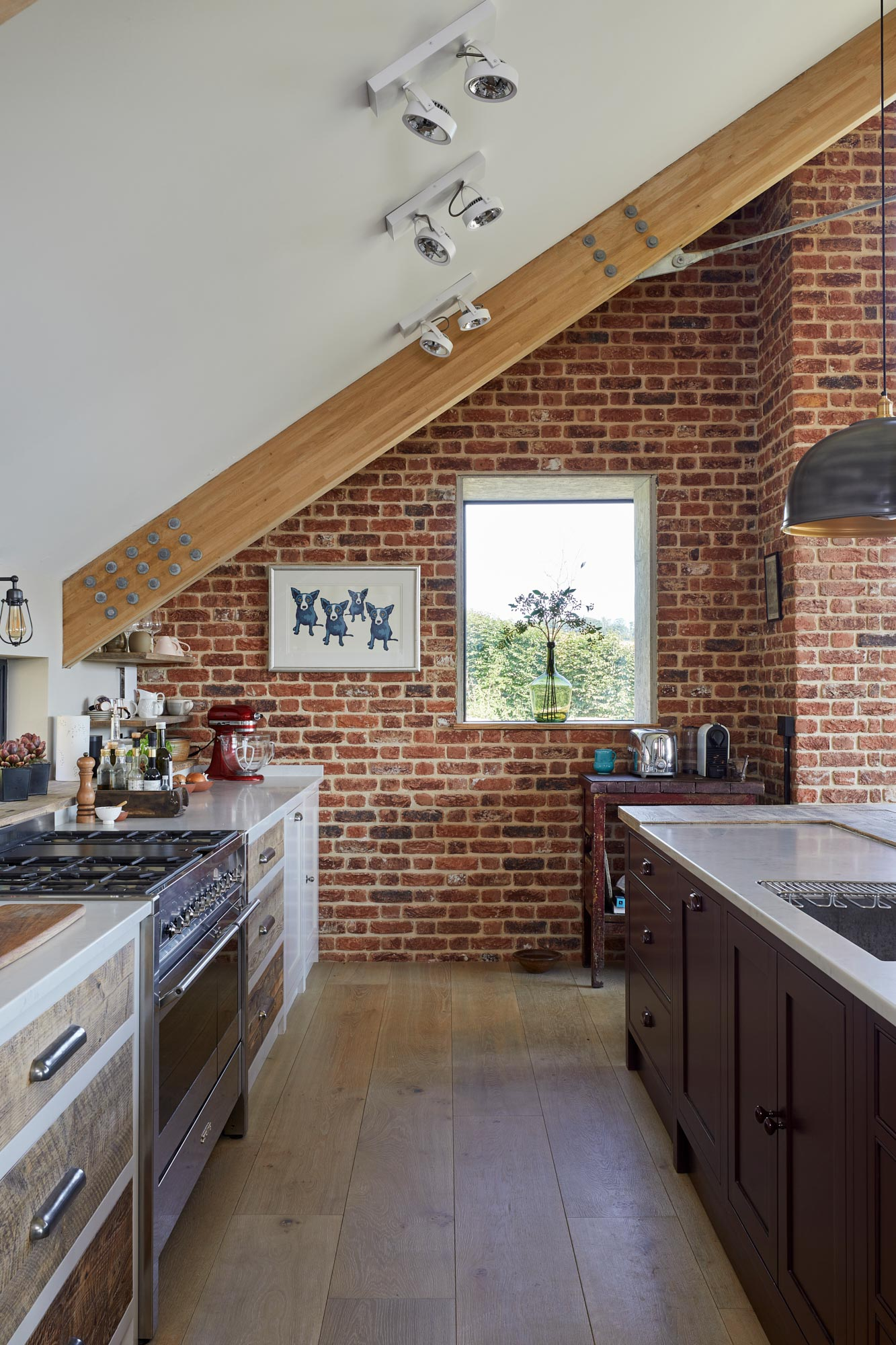 Exposed brick wall in kitchen with clean oak engineered flooring
